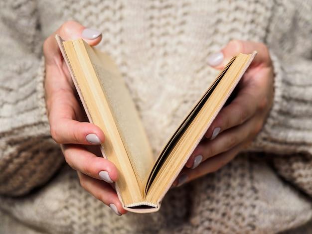 Boek in handen van vrouwen. een meisje in een wollen trui houdt een boek vast. gezellige sfeer. Premium Foto