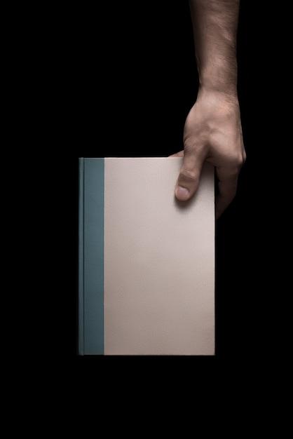 Boek in mannelijke handen op een zwarte achtergrond 3 van 7 Premium Foto