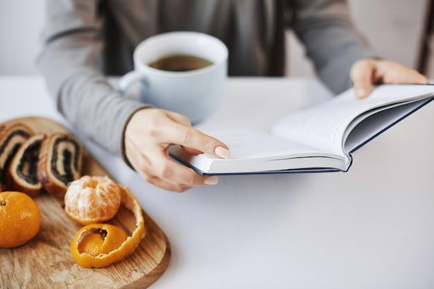Boek is als een kenniskamer. slimme moderne vrouw leest favoriete roman tijdens het ontbijt, geniet van het drinken van hete thee in een rustige en gezellige sfeer, schilt mandarijn en eet Gratis Foto