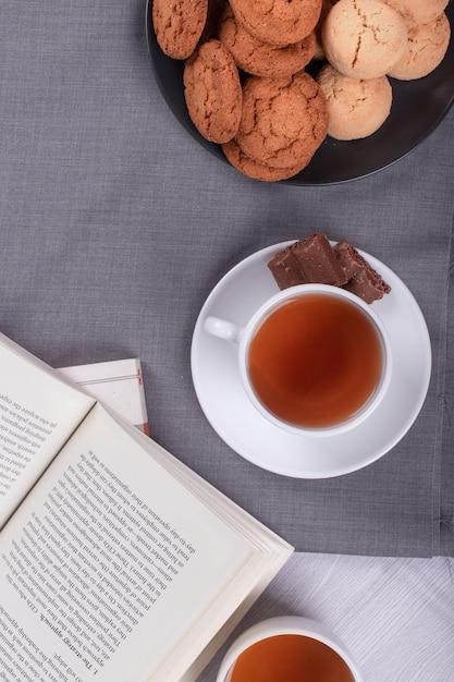 Boek, kopje thee en chocolade op de tafel Gratis Foto