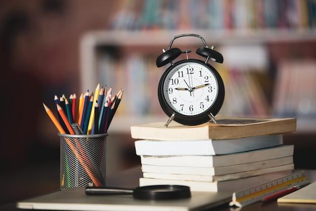 Boek, laptop, potlood, klok op houten tafel in bibliotheek, onderwijs leren concept Gratis Foto