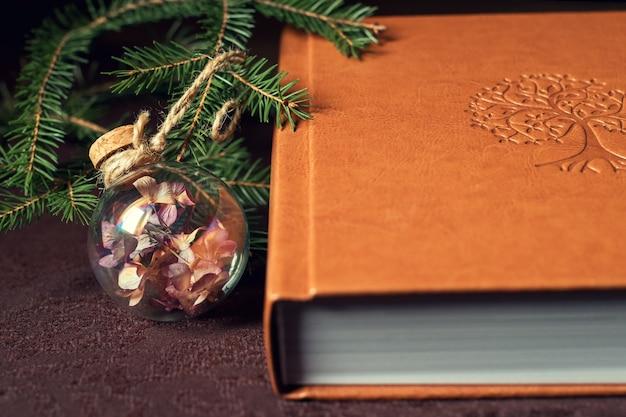 Boek onder de kerstboom versierd met glazen bol Premium Foto
