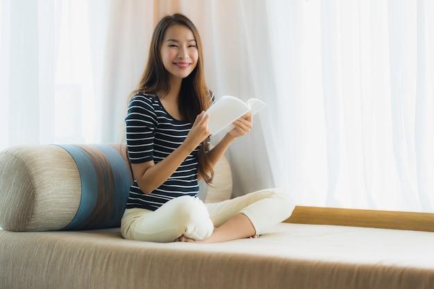 Boek van de de vrouwenlezing van de portret het mooie jonge aziatische binnen op bank op woonkamergebied Gratis Foto
