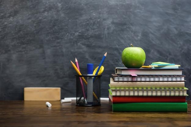 Boeken, briefpapier en educatieve benodigdheden op houten bureau in de klas Premium Foto