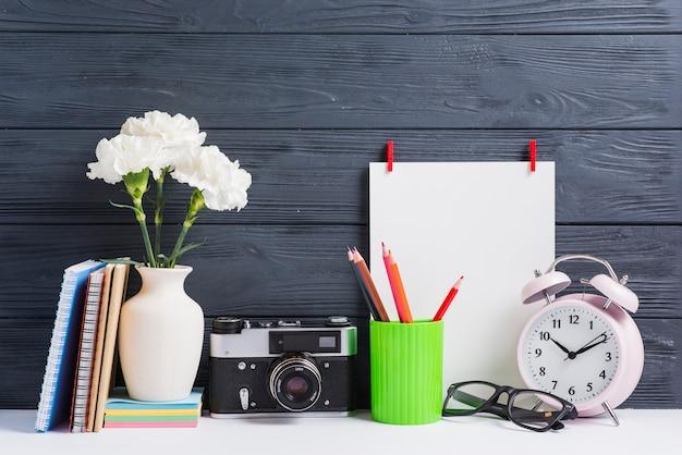 Boeken; vaas; vintage camera; bril; potlood houders en wit blanco papier op houten achtergrond Gratis Foto