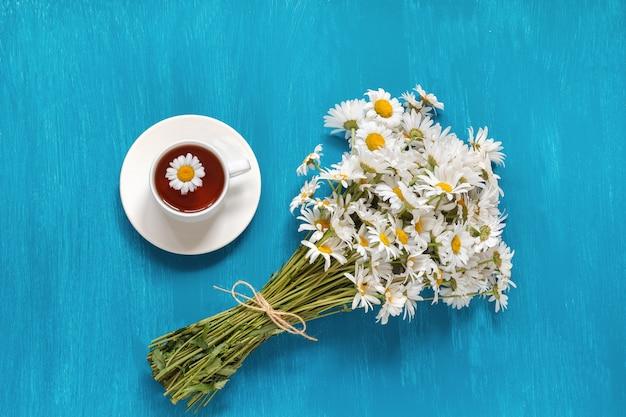 Boeket bloemen veld chamomiles kopje kruidenthee op blauwe woode Premium Foto