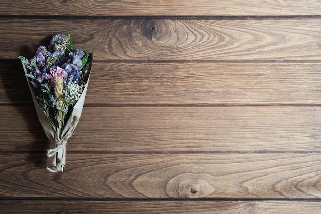 Boeket gedroogde wilde bloemen op rustieke houten tafel achtergrond Premium Foto