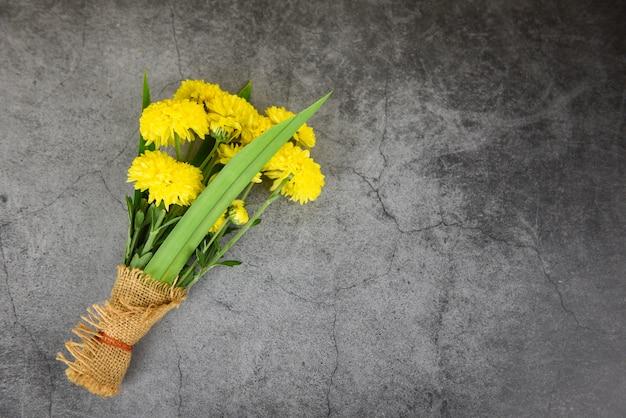 Boeket gele mum bloemen lente en pandan verpakt in zak op donkere plaat achtergrond Premium Foto