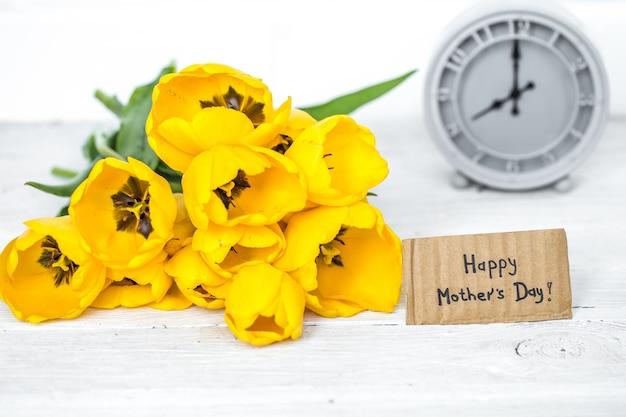 Boeket gele tulpen en een retro klok op een lichte houten achtergrond, ruimte voor tekst, concept van de vakantie Gratis Foto