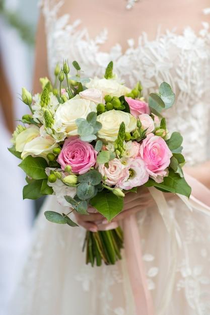 Boeket in handen van de bruid van verse rozen Premium Foto