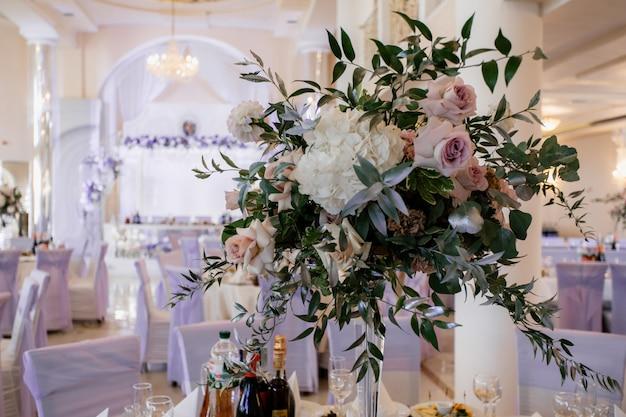 Boeket met bloemen en groen versierd staan op de feesttafel Gratis Foto