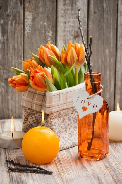Boeket oranje tulpen, aangestoken kaarsen Premium Foto