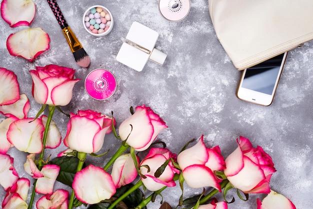 Boeket rozen met cosmetica in parfum op een grijze achtergrond met kopie ruimte Premium Foto