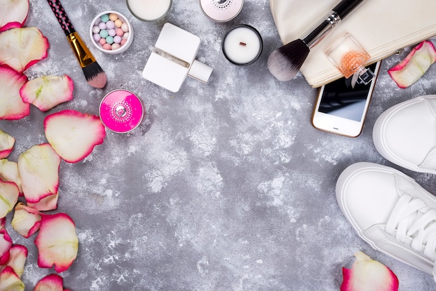 Boeket rozen met cosmetica in parfum, telefoon en sneakers op een grijze achtergrond Premium Foto