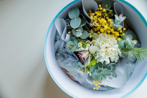 Boeket van bloeiende mimosa, anjer. kopieer ruimte. bovenaanzicht van een levendig boeket. aanwezig voor speciale gebeurtenis Premium Foto