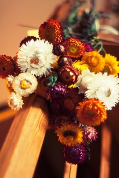Boeket van bloemen op een houten balk Gratis Foto