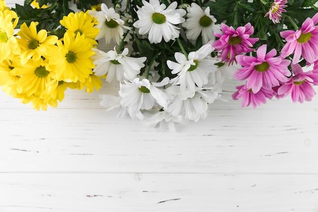 Boeket van geel; witte en roze madeliefjebloemen op witte houten geweven achtergrond Gratis Foto
