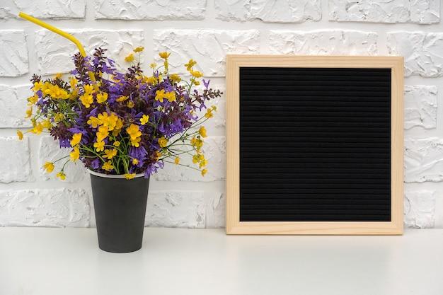 Boeket van gekleurde bloemen in zwart papier koffiekopje met cocktailstro en lege zwarte letter boord op tafel Premium Foto