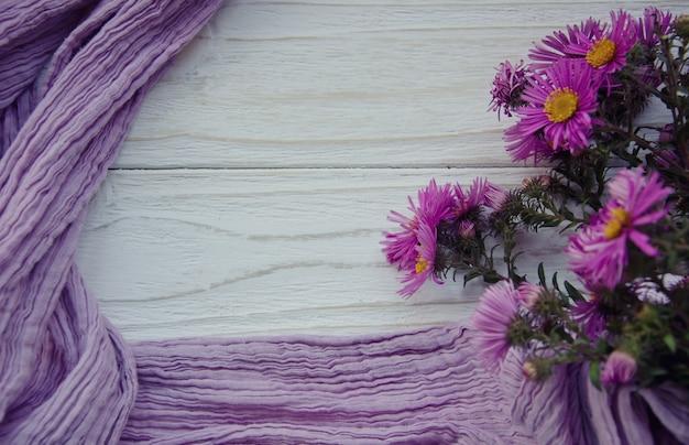 Boeket van heldere herfstbloemen en een paarse sjaal die een frame vormt Premium Foto