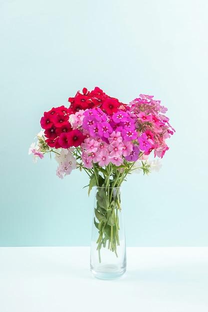 Boeket van kleurrijke bloemen in vaas op blauwe achtergrond. kopieer ruimte minimalistische stijl. sjabloon voor briefkaart, tekst, ontwerp Premium Foto