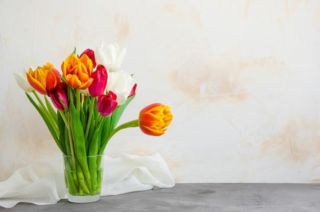 Boeket van kleurrijke natuurlijke tulpen in een glazen vaas met water op een betonnen achtergrond. Premium Foto
