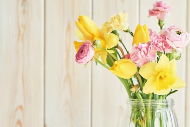 Boeket van lentebloemen: tulpen, anjers, ranunculi en narcissen in vaas op tafel. moederdag groet Premium Foto