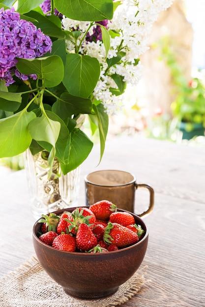 Boeket van lila takken in kristallen vaas, klei kom met rode aardbei en donkere glazen beker op houten tafel. Gratis Foto
