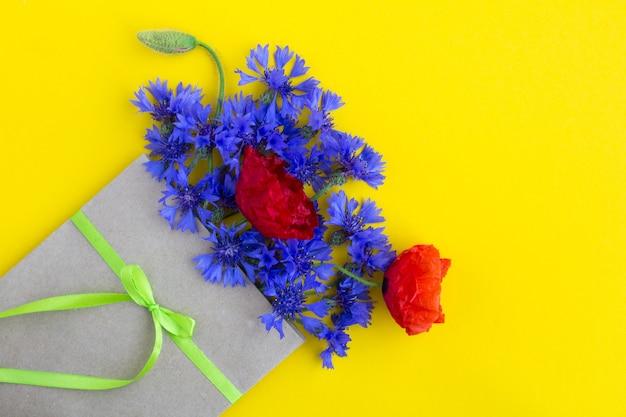 Boeket van rode papavers en blauwe korenbloemen in een envelop op geel Premium Foto