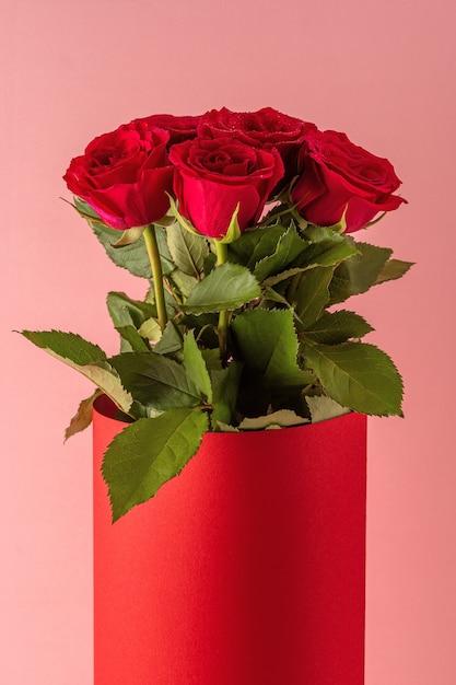Boeket van rode rozen in rode pot op roze achtergrond. Premium Foto