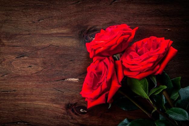 Boeket van rode rozen op een gestructureerde houten achtergrond, vrije ruimte voor tekst Premium Foto
