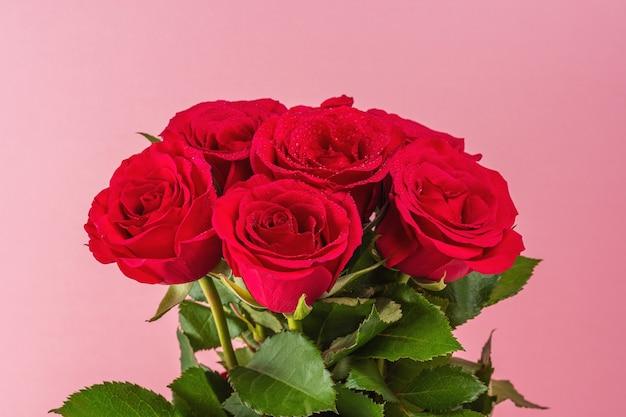 Boeket van rode rozen op roze achtergrond. Premium Foto