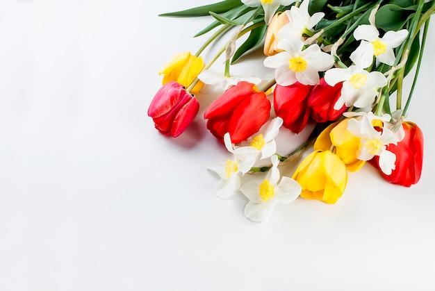 Boeket van rode tulpen, narcissen en cadeau op de witte achtergrond Premium Foto
