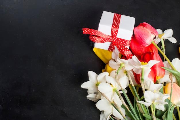 Boeket van rode tulpen, narcissen en cadeau op de zwarte achtergrond Premium Foto
