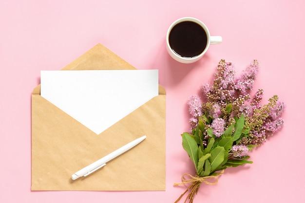 Boeket van roze bloemen, envelop met witte lege kaart Premium Foto