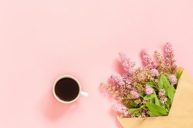 Boeket van roze bloemen in envelop, kopje koffie en een witte lege kaart voor tekst op roze achtergrond Premium Foto