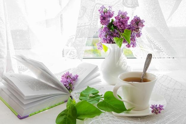 Boeket van roze bloemen (rozen) en witte service op een vensterbank. Premium Foto