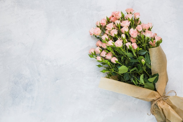 Boeket van roze rozen gewikkeld in bruin papier met string op betonnen muur Gratis Foto