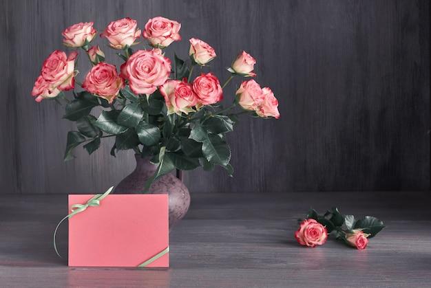 Boeket van roze rozen op donkere rustieke achtergrond met kopie-ruimte op blanco papier kaart Premium Foto