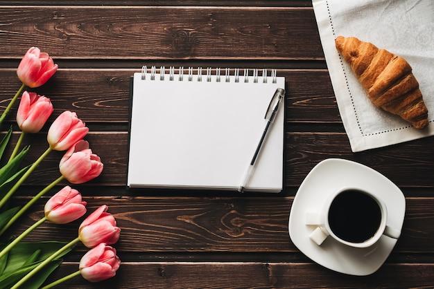 Boeket van roze tulpen met een kopje koffie en een croissant Premium Foto