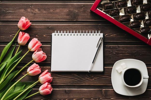 Boeket van roze tulpen met een kopje koffie en een doos chocolaatjes op een houten tafel Premium Foto