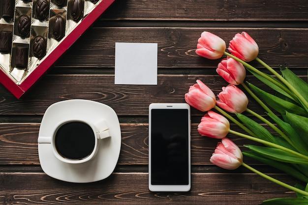 Boeket van roze tulpenbloemen met een kopje koffie, een doos chocolaatjes en een smartphone Premium Foto