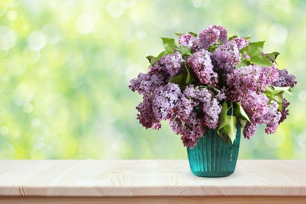Boeket van seringen op een houten tafel. bloemen in een vaas op vage de lenteachtergrond met bokeh. Premium Foto