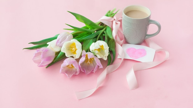 Boeket van tulpen en een koffiekopje op een roze pastel achtergrond. Premium Foto