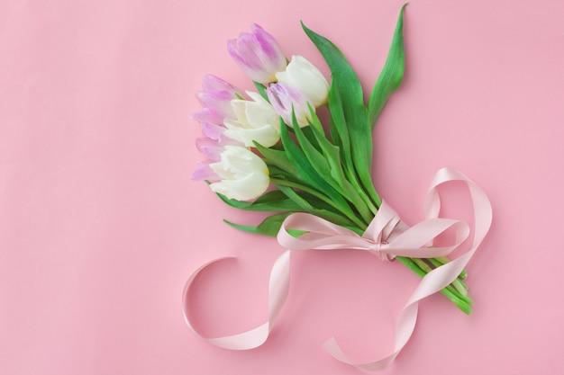 Boeket van tulpen op een roze pastel achtergrond. Premium Foto