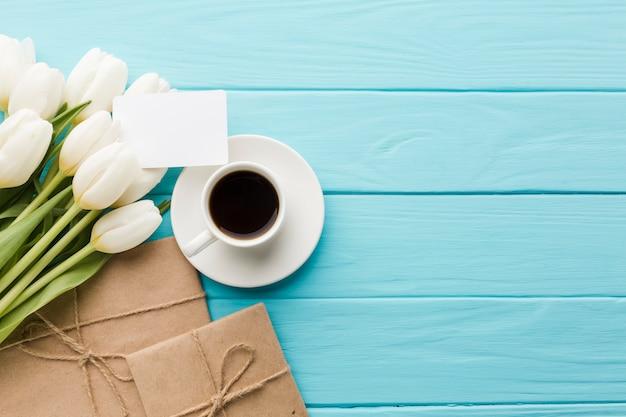 Boeket van tulpenbloemen met koffie en verpakt papier Gratis Foto