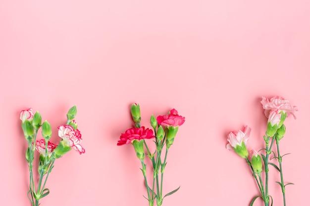 Boeket van verschillende roze anjerbloemen op roze achtergrond Premium Foto