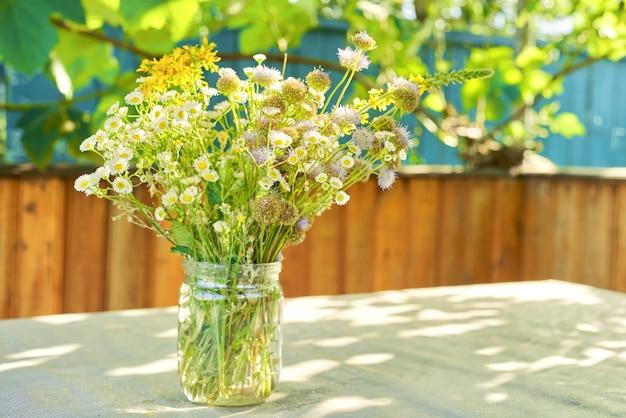 Boeket van wilde zomerbloemen en kruiden in pot op tafel op terras Premium Foto