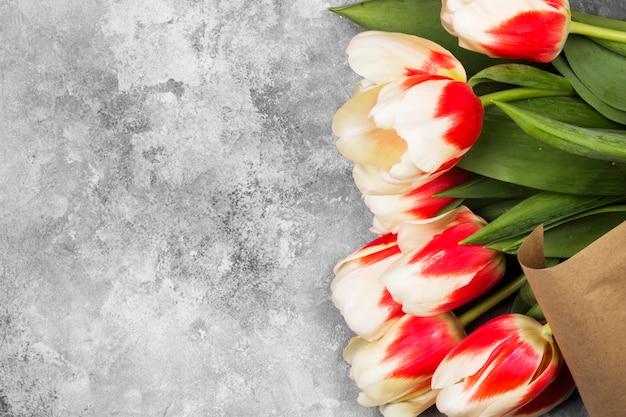 Boeket van witte roze tulpen op een grijze achtergrond. bovenaanzicht, kopie ruimte Premium Foto