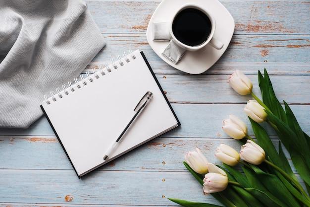 Boeket van witte tulpen met een lege laptop, een kopje koffie op een houten achtergrond Premium Foto