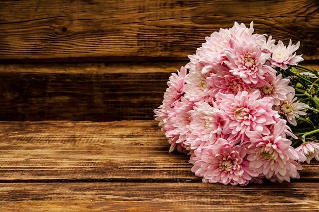 Boeket van zachtroze chrysanten. mooi cadeau op vintage houten achtergrond Premium Foto